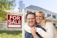 Pares na frente da casa nova e do sinal de Real Estate Imagem de Stock