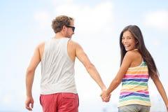 Pares na moda novos alegres felizes que guardaram as mãos Imagem de Stock Royalty Free