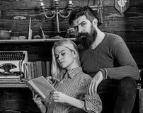 Pares na poesia da leitura do amor na atmosfera morna Senhora e homem com a barba nas caras sonhadoras com livro, leitura românti fotos de stock royalty free