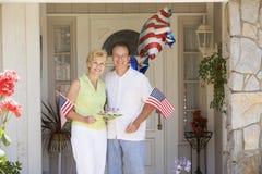 Pares na porta da rua no quarto de julho com bandeiras Imagens de Stock Royalty Free