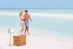 Pares na praia com Champagne Picnic luxuoso imagem de stock royalty free