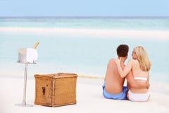 Pares na praia com Champagne Picnic luxuoso Imagens de Stock Royalty Free