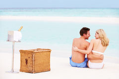 Pares na praia com Champagne Picnic luxuoso Fotos de Stock Royalty Free