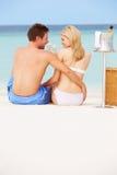 Pares na praia com Champagne Picnic luxuoso foto de stock royalty free