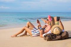 Pares na praia com telefones celulares Fotos de Stock Royalty Free
