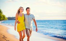Pares na praia no por do sol fotografia de stock
