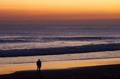 Pares na praia por surfistas de observação do crepúsculo Imagem de Stock Royalty Free
