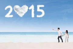 Pares na praia que aponta no número 2015 foto de stock
