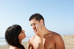 Pares na praia que põr sobre o creme Fotografia de Stock