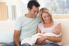 Pares na sala de visitas com bebê imagem de stock