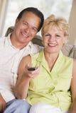 Pares na sala de visitas usando o sorriso de controle remoto fotografia de stock royalty free