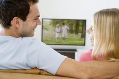 Pares na televisão de observação da sala de visitas Imagens de Stock Royalty Free
