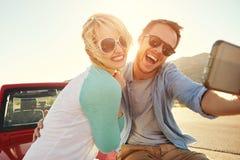 Pares na viagem por estrada Sit On Convertible Car Taking Selfie fotos de stock royalty free