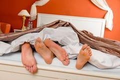 Pares Napping que mienten descalzo bajo cama de las cubiertas fotografía de archivo