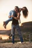 Pares nas calças de brim na praia Fotografia de Stock Royalty Free