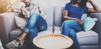Pares negros descontentados jóvenes Hombres africanos americanos que discuten con su novia, al lado de quien se está sentando en  Imagenes de archivo