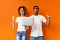 Pares negros emocionados que celebran triunfo con el ordenador portátil foto de archivo libre de regalías