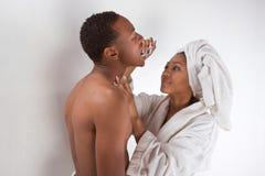 Pares negros envueltos en dientes que aplican con brocha de la toalla de baño Fotos de archivo libres de regalías