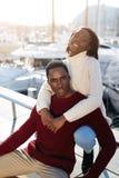pares negros felices que disfrutan del tiempo que pasa junto mientras que se sienta en el puerto del yate de Barcelona Foto de archivo