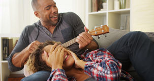 Pares negros felices que mienten en el sofá con el ukelele Imagen de archivo