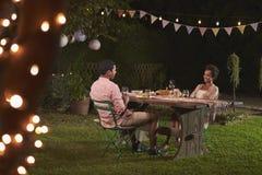 Pares negros jovenes que se relajan en la cena en un jardín Foto de archivo libre de regalías
