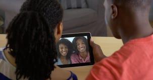 Pares negros que hablan con los amigos sobre la charla video de la tableta Imágenes de archivo libres de regalías