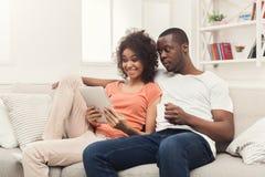 Pares negros que hacen usando la tableta digital en casa imágenes de archivo libres de regalías