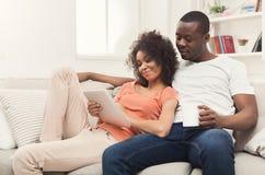 Pares negros que hacen usando la tableta digital en casa imagen de archivo libre de regalías