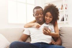 Pares negros que hacen usando smartphone en casa fotos de archivo libres de regalías