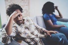 Pares negros tristes jovenes Hombre trastornado que es ignorado por el socio en casa en la sala de estar Hombres africanos americ Foto de archivo libre de regalías