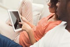 Pares negros usando la tableta digital en casa imagenes de archivo