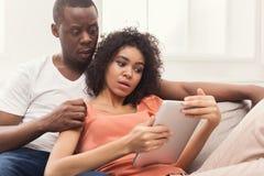 Pares negros usando la tableta digital en casa fotografía de archivo libre de regalías