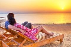 Pares no abraço que olha junto o nascer do sol sobre S vermelho Imagens de Stock Royalty Free