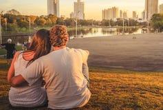 Pares no amor assentados na grama uma ao lado de outro no parque imagem de stock royalty free