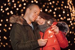 Pares no amor com os chuveirinhos na noite da cidade do inverno fotografia de stock royalty free