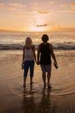 Pares no amor e mãos guardar na praia no por do sol fotografia de stock royalty free