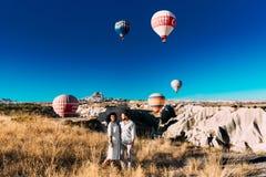 Pares no amor entre bal?es Pares felizes em Cappadocia Lua de mel nas montanhas Viagem do homem e da mulher Voo em bal?es imagem de stock royalty free