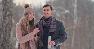 Pares no amor na floresta do inverno para beber o chá de uma garrafa térmica Homem e mulher à moda em um revestimento no parque n filme