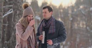 Pares no amor na floresta do inverno para beber o chá de uma garrafa térmica Homem e mulher à moda em um revestimento no parque n video estoque