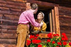 Pares no amor na janela da cabana da montanha Fotografia de Stock