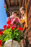 Pares no amor na janela da cabana da montanha Fotografia de Stock Royalty Free
