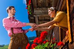 Pares no amor na janela da cabana da montanha Foto de Stock Royalty Free