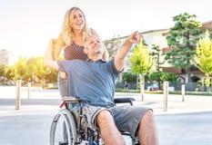 Pares no amor no centro da cidade homem com o desease em uma cadeira de rodas e em sua mulher bonita Fotografia de Stock Royalty Free