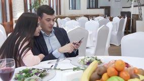 Pares no amor no restaurante que consulta redes sociais em um vídeo da metragem do estoque do iPhone video estoque