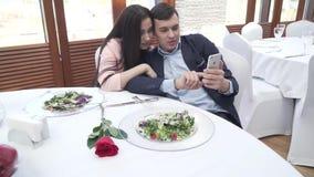 Pares no amor no restaurante que consulta redes sociais em um vídeo da metragem do estoque do iPhone filme