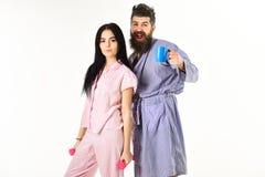 Pares no amor no pijama, suporte do roupão isolado no fundo branco Pares, família nas caras sonolentos, completas da energia Imagem de Stock Royalty Free