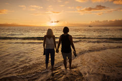 Pares no amor que anda ao longo da praia junto no por do sol Imagens de Stock