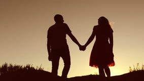 Pares no amor que anda no vídeo de movimento lento do por do sol da natureza da silhueta A silhueta do homem e da mulher de um am vídeos de arquivo