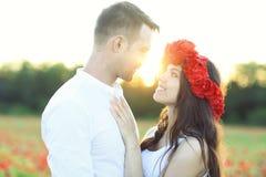 Pares no amor que beija e que abraça no campo da papoila Fotografia de Stock Royalty Free
