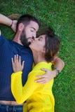 Pares no amor que beija na grama fotografia de stock